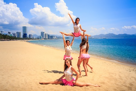 perform: cheerleaders in white pink uniform perform High Straddle Stunt on sand beach against sea wind shakes long hair Stock Photo