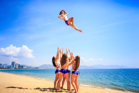squad of cheerleaders in white blue uniform performs stunt Basket Toss on beach against azure sea and resort Stock Photo