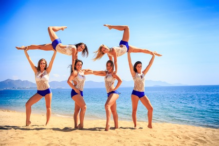 squad: squad of six cute cheerleaders in white blue uniform performs Swedish falls on beach against azure sea