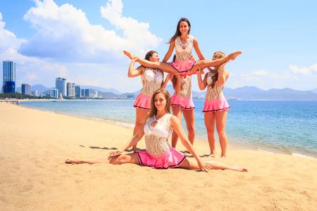 cheerleaders in white pink uniform perform Straddle Stunt one girl does split on sand beach against resort city
