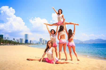 straddle: cheerleaders in white pink uniform perform High Straddle Stunt on sand beach against sea wind shakes long hair Stock Photo