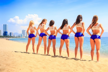 squad: squad of cheerleaders in white blue uniform stands backside view with hands on hips on beach wind shakes long hair