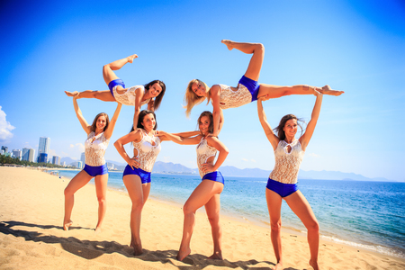 squad: squad of six cute cheerleaders in white blue uniform sideview performs Swedish falls on beach against azure sea