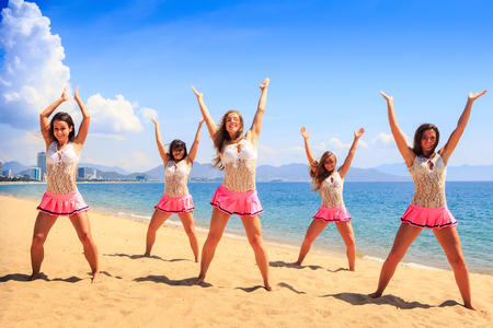 squad: squad of cheerleaders in white pink uniform dances on sand beach with hands upwards against sea wind shakes long hair Stock Photo