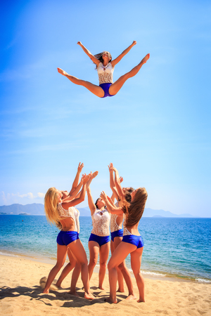 to toss: squad of cheerleaders in white blue uniform performs Toe Touch Basket Toss on beach against azure sea