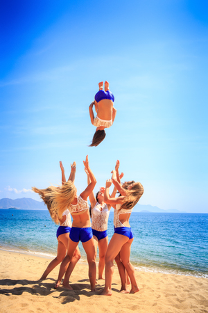 to toss: squad of six cute cheerleaders in white blue uniform performs Back Tuck Basket Toss on beach against azure sea