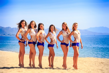 squad: squad of six cute cheerleaders in white blue uniform stands tip-toe in line on sand beach against azure sea Stock Photo