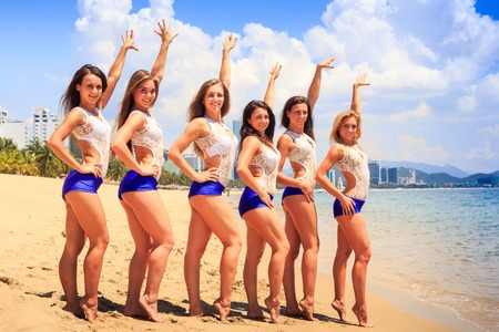 squad: cheerleaders in white blue uniform pose in line with hands upwards on sand beach against resort wind shakes long hair