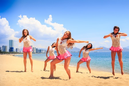 squad: cheerleaders in white pink uniform show dance pose with hands aside on sand beach against sea wind shakes long hair