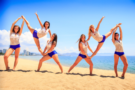 perform: cheerleaders in white blue uniform perform double Heel Stretch on sand beach smiles against sea wind shakes long hair