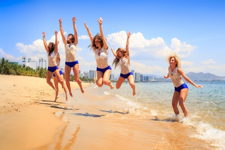 lift hands: cheerleaders in white blue uniform jump over shallow water lift hands and smile against azure sea wind shakes hair