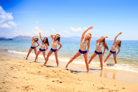 bent over: cheerleaders in white blue stand in triangle position with one hand bent over head on wet sand beach against azure sea Stock Photo