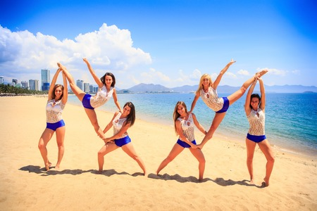 the double: cheerleaders in white blue uniform perform double Heel Stretch on sand beach smiles against sea wind shakes long hair