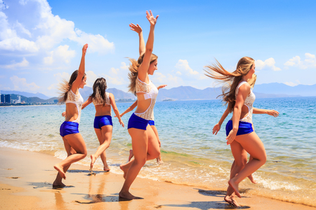 squad: squad of cheerleaders in white blue uniform runs with hands up into sea water against resort city wind shakes long hair