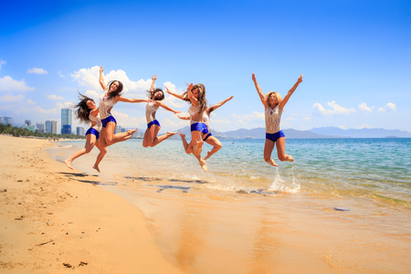 synchronous: cheerleaders in white blue uniform perform high synchronous jump over shallow water against sea wind shakes hair Stock Photo