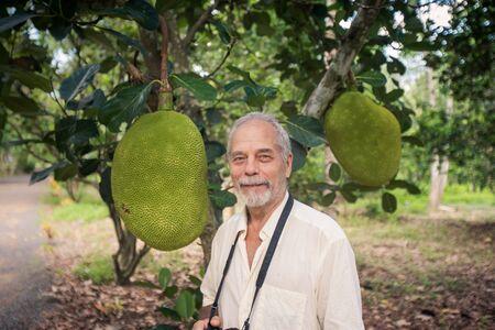 big shirt: closeup grey old man in white shirt between large jackfruit fruits against country garden