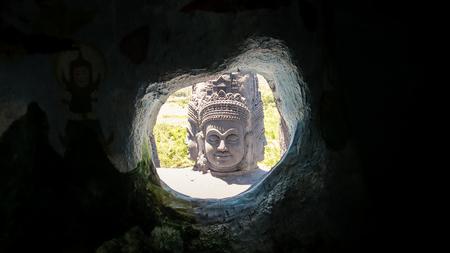 dark cave: panorama of large bright god head sculpture through dark cave exit