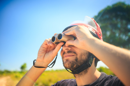 closeup bearded man in helmet watches sky through binocular against pictorial landscape