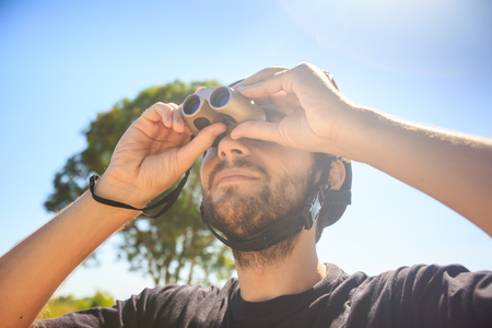 closeup bearded guy in T-shirt watches sky through binocular under bright sunlight