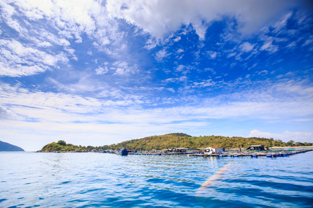panorama of azure sea green hill island against blue sky with big white clouds