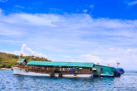closeup large tourist motor-boat at moorage near green hills shore against white clouds lace in blue sky Stock fotó