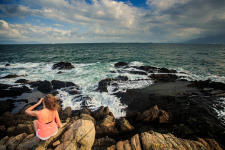 young blond girl in orange top sits on a rocky coast Stock Photo