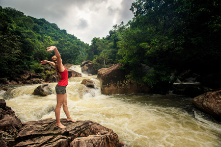 young blonde girl in vest shorts poses lifts hands on rock by tropical foamy mountain river Stock Photo
