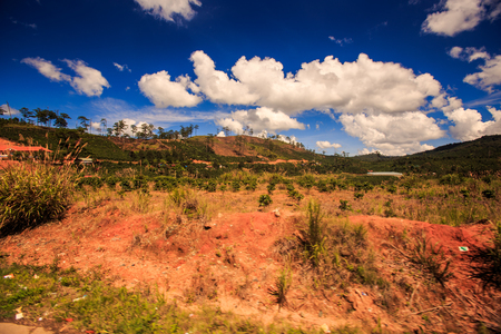 landscape of small stony brown hills with poor vegetation against cloudy blue sky