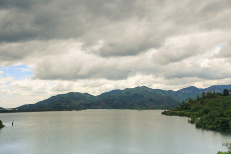 panorama of a large lake among hills and tropics under a cloudy gray sky in Vietnam