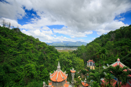 closeup pagoda red roofs on foreground among a hill tropical forest against a lake and cloudy blue sky in Vietnam Stock Photo