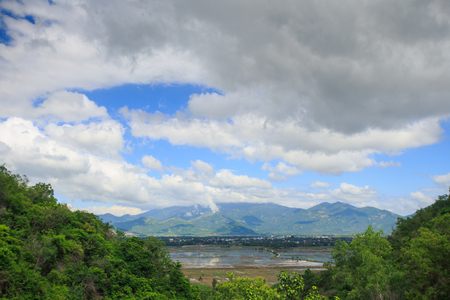 panorama of a lake among mountains and a tropical forest on a cloudy blue sky