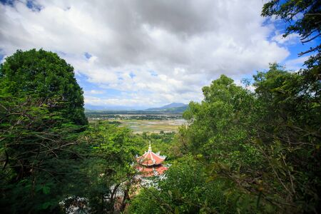 monastery pagoda red roof among tropical forest against lake and cloudy blue sky in Vietnam