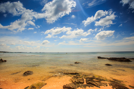 closeup flat transparent yellow stony sea bottom under low tide against azure sea and blue cloudy sky Stock Photo