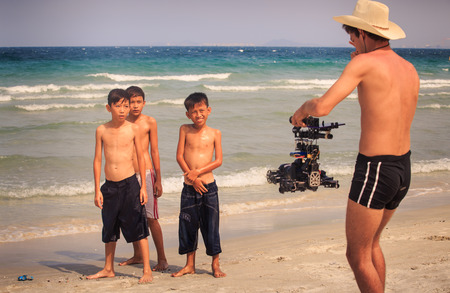 NHA TRANG / VIETNAM - APRIL 16 2017: European photographer in hat asks Vietnamese children to pose at camera boys on shy on ocean beach on April 16 in Nha Trang
