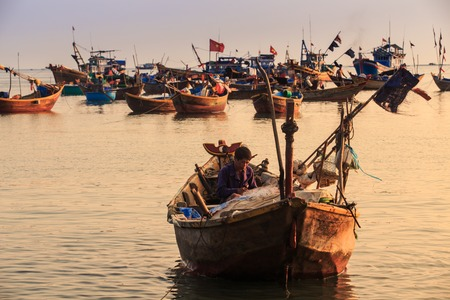 MUI NE  VIETNAM - MARCH 17 2016: Asian fisherman sits in big boat with different fishing tackle against other boats and clear sky at sunset on March 17 in Mui Ne