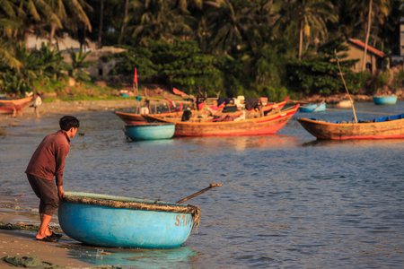 MUI NE  VIETNAM - MARCH 17 2016: Barefoot asian man pushes blue round fishing boat on March 17 in Mui Ne