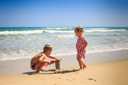 side view little blond girl with pigtails in spotty pink dress stands elder boy squats on wet edge of beach 스톡 콘텐츠