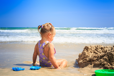 closeup backside view little blond girl with pigtails sits by sand heap plays on beach against shallow wave surf