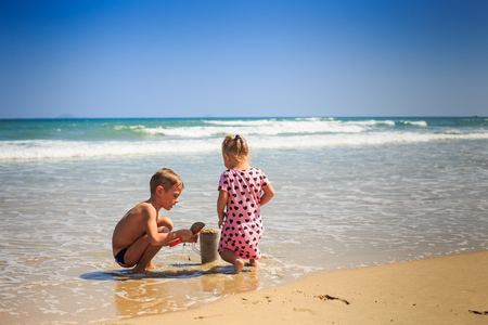 backside view little blond girl with pig-tails in spotty pink dress elder boy play on wet edge of wave surf of beach 스톡 콘텐츠