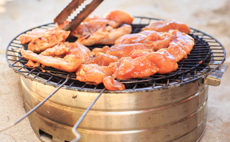 closeup chicken wings cooking on barbecue grating on beach Stock Photo
