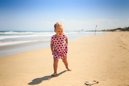 little blond girl with pigtails in spotty pink dress standing by azure sea wave sur at looks at left glove on beach