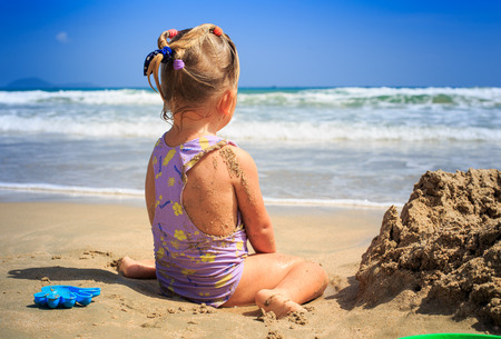 closeup backside view little blond girl with pigtails in swimsuit sits on sand