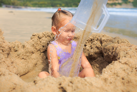 closeup little blond girl sits in the hole among sand heap behind water flow wall from mug on beach