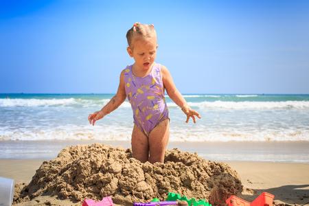 little blonde girl in swimsuit standing on wet sand heap on sea beach against blue sky