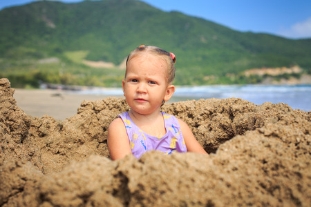 closeup little blonde girl sits in a sand hole from a mug on an ocean beach against a blue sea Imagens