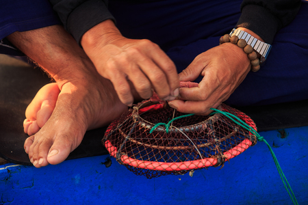 closeup of barefoot old man fishing basket with hands on bracelets on blue background in Vietnam