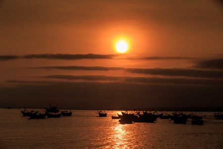 pictorial panorama sunset sun disk lights fishing boat silhouettes in ocean bay against boundless dark sky