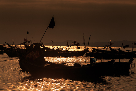 dark local fishing boat silhouettes against sunset reflection on ocean bay water surface at dusk