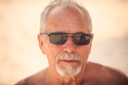 portrait of gray haired bearded old man in modern black sunglasses against light background