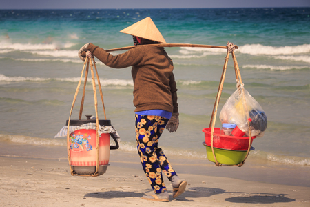 closeup backside Vietnamese fruit vendor woman in hat with bucket on yoke walks along sand beach against azure sea